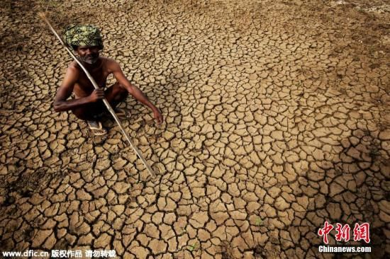 当地时间2015年5月26日,印度Doddaballapur,一名农民坐在龟裂的土地上。