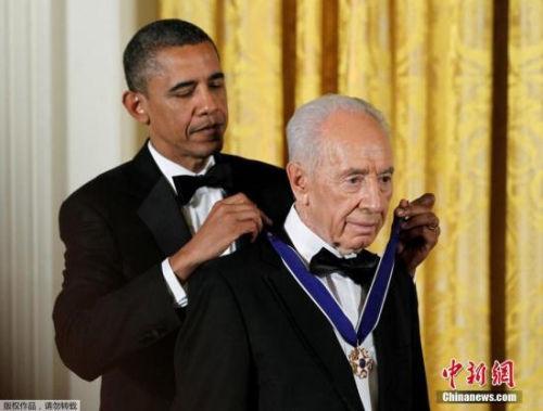 当地时间9月28日,以色列前总统佩雷斯因病去世,享年93岁。图为2012年6月13日美国总统奥巴马为佩雷斯佩戴自由勋章。