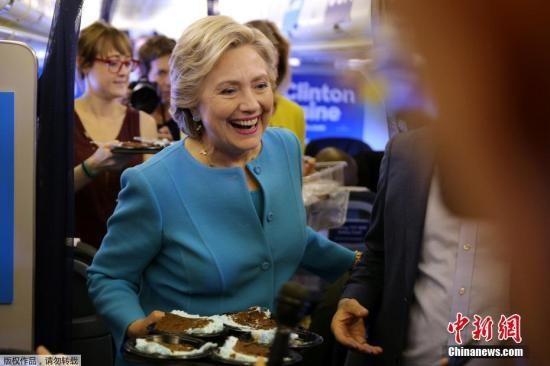 当地时间2016年10月26日,美国,26日是希拉里的69岁生日。飞往纽约的竞选专机上,希拉里向随行的媒体记者们派送生日蛋糕。