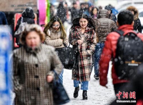 3月20日,受冷空气影响,新疆乌鲁木齐市降下纷纷扬扬的雪花,气温也随之骤降。图为民众冒雪出行。 中新社记者 刘新 摄