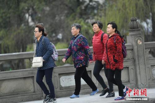 3月14日,四川成都街头行人身着厚衣物出行。受北方冷空气影响,四川盆地连日来气温持续走低,局部还出现了降雪天气,民众纷纷添加厚衣物御寒。 中新社记者 张浪 摄