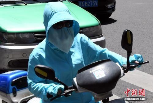 """7月10日,福建省福州市民出行""""全副武装""""抵挡酷暑。刘可耕 摄"""