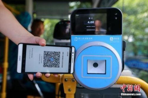 智能手机使用场景越来越多。图为民众乘坐交通工具出行时使用手机支付。中新社发 许康平 摄