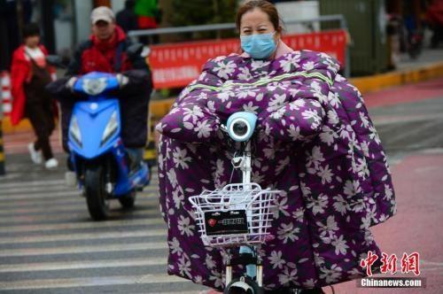 """10月9日,内蒙古多地大幅降温,在呼和浩特街头,骑电动车的行人穿上""""棉衣""""出行。 中新社记者 刘文华 摄"""