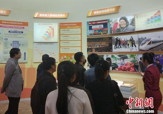 """民众在参观""""以人民为中心 增进人民获得感""""展区。中新网记者 李金磊 摄"""
