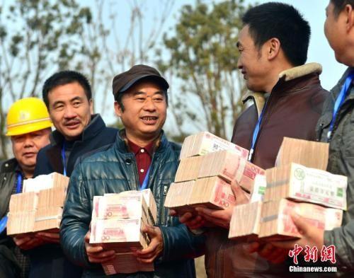 资料图:刚刚领到工资的农民工们。图片来源:视觉中国