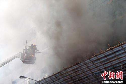 11月9日,香港新蒲岗景福街启德工厂大厦二楼起火,现场冒出大量浓烟,消防员架起云梯扑救。中新社记者 谭达明 摄