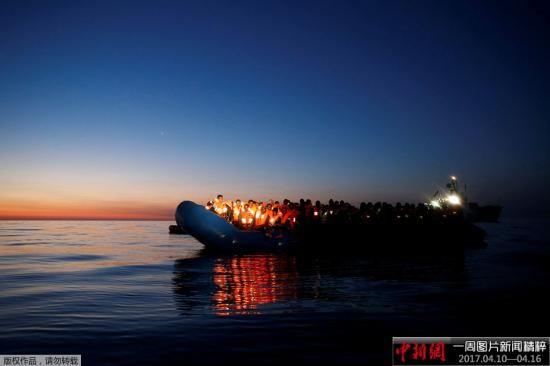 当地时间2017年4月15日,地中海的黎明里,一艘等待被救援的难民船飘在海上。