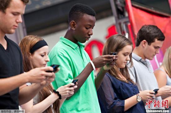资料图:当地时间2012年8月8日,美国纽约,第6届发短信大赛在时代广场上举行,选手们运指如飞。
