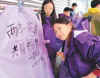 """图为参与活动的小朋友在天灯上写下""""两岸一家亲,共圆中国梦""""的祝福语。李俞柔摄"""