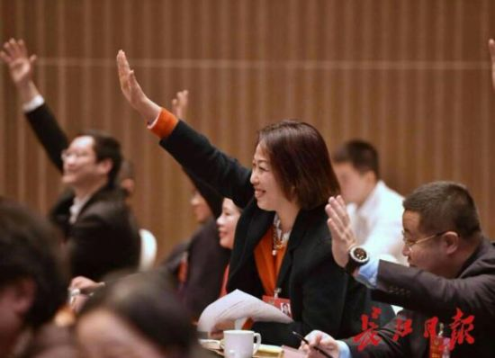 1月11日,在与政协委员协商座谈会上,政协委员踊跃举手争取发言机会。 记者 郭良朔 摄