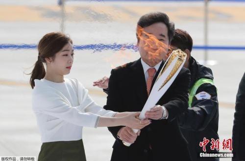 资料图:韩国总理李洛渊(右)、平昌冬奥宣传大使金妍儿(左)手持圣火。