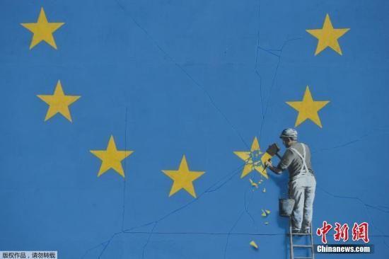 资料图:街头艺术家班克西创作了一幅画,画面中一名工人正从欧盟12星旗帜上抹掉一颗星,寓意着英国将脱离欧盟。