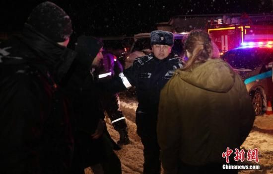 当地时间2月11日,一名警察在阻挡媒体记者通过警方为坠机地点设置的警戒线。 中新社记者 王修君 摄