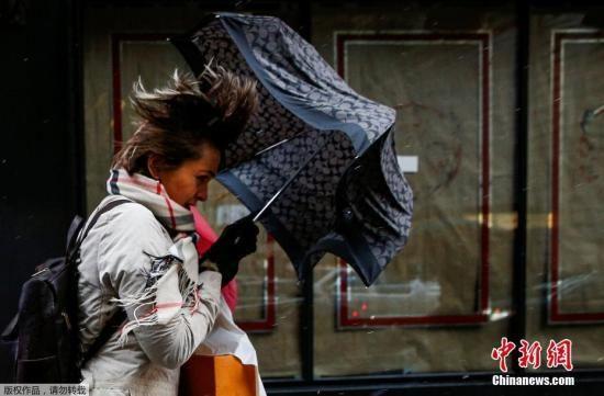 """图为此前""""炸弹气旋""""袭击美国期间,纽约民众顶着强风走在时代广场上。"""