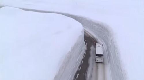资料图:旅游大巴通过高耸的雪墙。(图片来源:立山黑部阿尔卑斯山脉旅游路线官方网站视频截图)