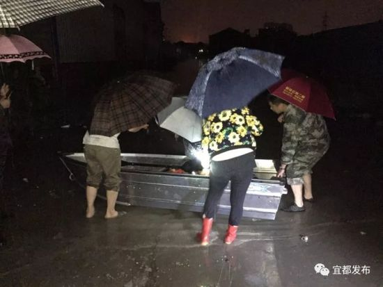 解放社区干部划船给受困居民送物资。