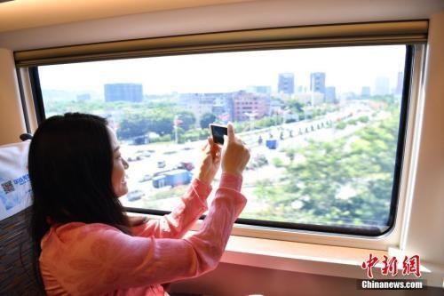 """图为""""复兴号""""高铁旅客拿手机拍摄窗外景色。 中新社记者 陈文 摄"""