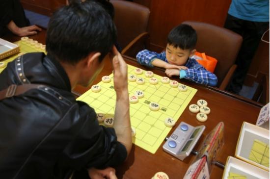 年龄最小的选手仅7岁,和自己爷爷年龄相仿者对弈,沉着冷静,从容不迫。
