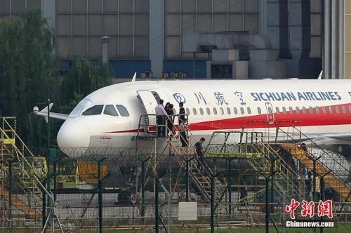 5月14日17时,成都机务人员正在对注册号为B-6419的空客A319客机进行检查,破损的右侧风挡玻璃处已经被临时遮挡。汪龙华 摄