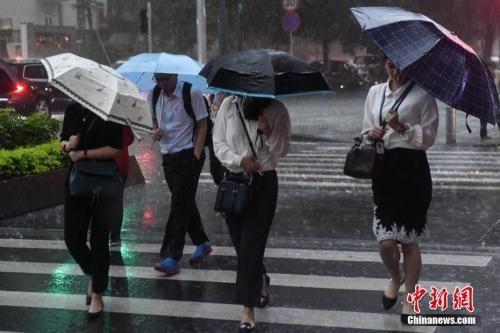 资料图:5月7日,广州街头,民众撑伞行走在雨中。中新社记者 陈骥�F 摄
