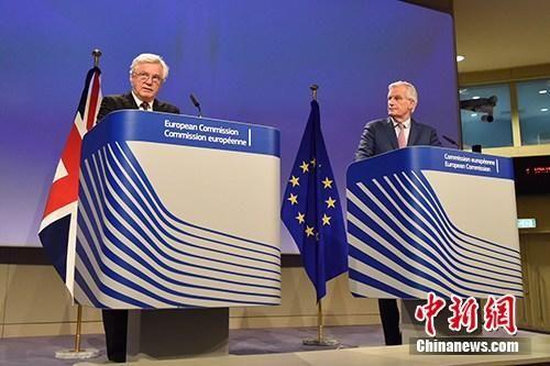 """当地时间3月19日,脱欧谈判欧盟首席谈判代表巴尼耶(图右)与英国脱欧事务大臣戴维斯(图左)共见记者,宣布双方迈出""""决定性一步"""",就脱欧过渡期安排等议题达成协议,但棘手的英国北爱尔兰与爱尔兰边界问题仍悬而未决。中新社记者 德永健 摄"""