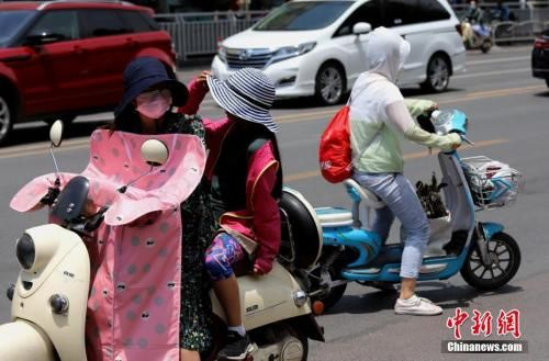 """资料图:6月6日,河南郑州遭遇高温天气,出行民众""""全副武装""""遮阳防晒。中新社记者 王中举 摄"""