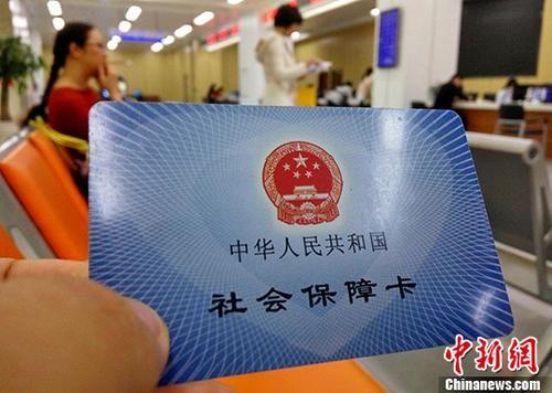 民众展示自己的社会保障卡。(资料图片)中新社记者 张斌 摄