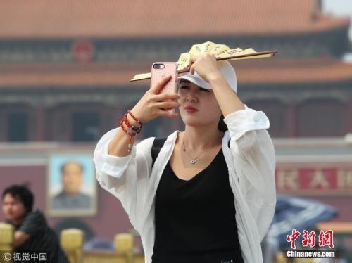6月26日,北京,游客遮阳防晒各有各招。当天北京最高气温达36度。图片来源:视觉中国
