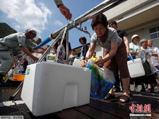 当地时间7月9日,日本广岛三原居民在被洪水淹没地区附近一个紧急供水站接水。