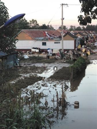 8月23日下午,口子村积水开始退去,村内留下大量淤泥。新京报记者 王文秋 摄