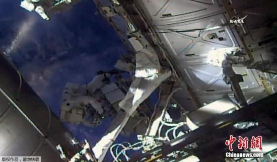 资料图:国际空间站上两名宇航员出舱太空行走,更换检查两个外置冷却箱。(视频截图)