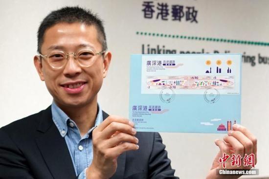 """9月13日,距离广深港高铁正式通车还有10天,香港邮政举行记者会,宣布一套以""""广深港高速铁路香港段""""为主题的特别邮票及相关集邮品将于9月17日推出发售,以资纪念。这套邮票形象鲜明,以高铁列车的夺目颜色和流线设计贯串四枚邮票,并由左至右分别展示广州、深圳和香港的特色。邮票上的列车有代表广、深、港三地文化和地标的图案,列车中段更化成两只牵着的手,象征香港与内地在经济及其他方面的交流,将随着广深港高铁香港段通车后更为密切,携手开拓新机遇。图为香港邮政高级经理李振宇展示贴有特别邮票小全张并以特别邮戳盖销的首日封。中新社记者 张炜 摄"""