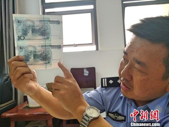 民警指出真钞与假钞的区别 杜勇 摄