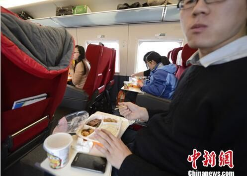 资料图:G801次列车一等座席的乘客在品尝列车提供的餐食。中新社发 侯宇 摄