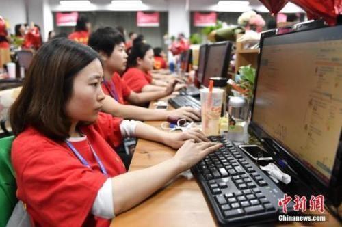资料图:某电商企业员工们在电脑前解答消费者的购物疑问。中新社记者 陈骥�F 摄