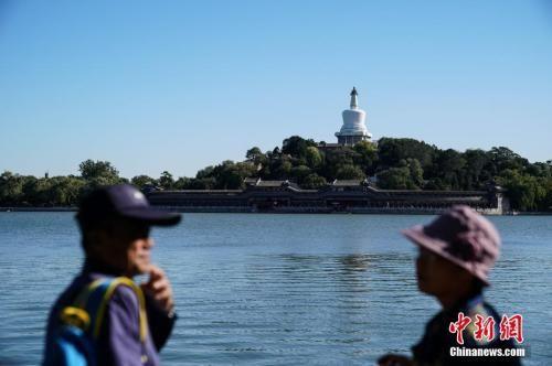 10月6日,北京迎来大风天气。图为游人在北海公园游玩。中新社记者 崔楠 摄
