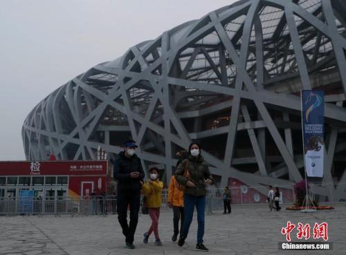 10月14日,游客在北京国家体育场附近游玩。北京市环境保护监测中心的实时监测数据显示,当日19时北京空气质量达重度污染,首要污染物为PM2.5。中新社记者 刘关关 摄
