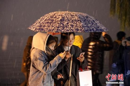资料图:杭州普遍降雪,游客在断桥前游览。中新社记者 毛建军 摄