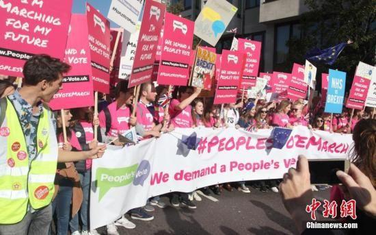 """10月20日,67万英国民众汇集在伦敦议会广场举行示威游行活动,呼吁对英国脱欧最终协议举行全民投票。图为示威游行队伍拉着横幅、举着标语牌,呼吁""""人民投票""""。中新社记者 张平 摄"""