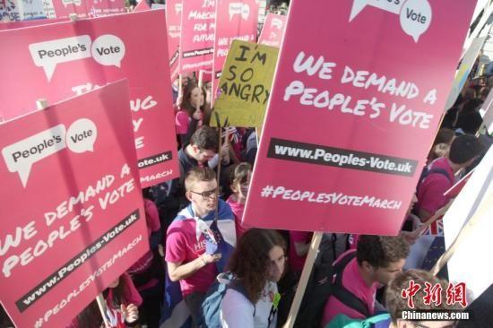 """2018年10月20日,67万英国民众汇集在伦敦议会广场举行示威游行活动,呼吁对英国脱欧最终协议举行全民投票。图为示威游行人群高举标语牌,呼吁举行""""人民投票""""。中新社记者 张平 摄"""