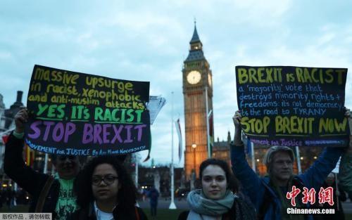 """资料图:当地时间2017年3月13日,英国伦敦,民众在国会大厦前聚集示威。英国议会上院投票通过""""脱欧""""法案,这为英国正式启动""""脱欧""""扫清了法律障碍。英国首相在获得英国女王授权后,即可启动""""脱欧""""。"""