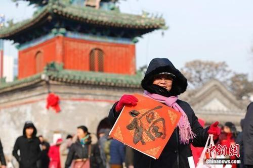 资料图:农历腊月廿三小年儿来临,北京东岳庙举办迎新春送春联活动,参与者甚众。中新社记者 富田 摄
