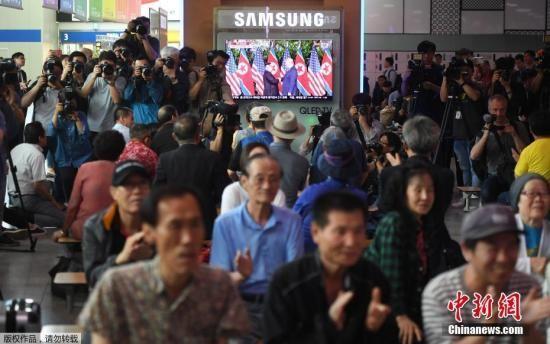 资料图:韩国首尔的一个火车站里,人们在观看金正恩与特朗普会晤直播的时候鼓掌。