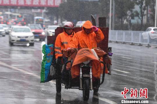 资料图:两位环卫工人在风雪中前行。 杨华峰 摄
