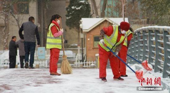 资料图:环卫工人正在清理道路积雪。中新社记者 李培源 摄