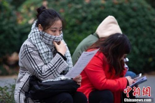 资料图:考生在南京林业大学考点等候进场时复习。中新社发 苏阳 摄 图片来源:CNSPHOTO