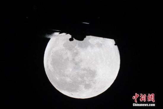 """资料图:一架飞机经过""""超级月亮""""。韦亮 摄"""