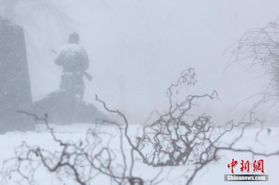 """资料图:当地时间2018年1月4日,暴雪中纽约法拉盛公园中的雕塑。当日,纽约降下2018年首场暴雪。受一波被称为""""炸弹气旋""""的风暴影响,美国东北部地区当天普遍遭受暴雪袭扰,3000多个航班因此取消。 中新社记者 廖攀 摄"""