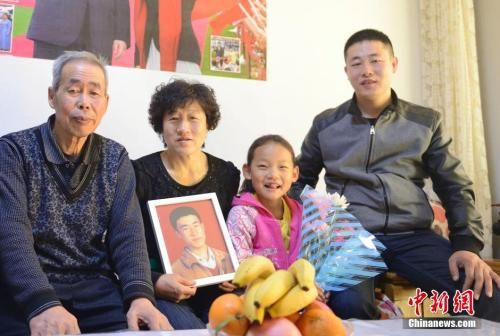 呼格吉勒图父母与呼格画像合影。中新社发 刘文华 摄
